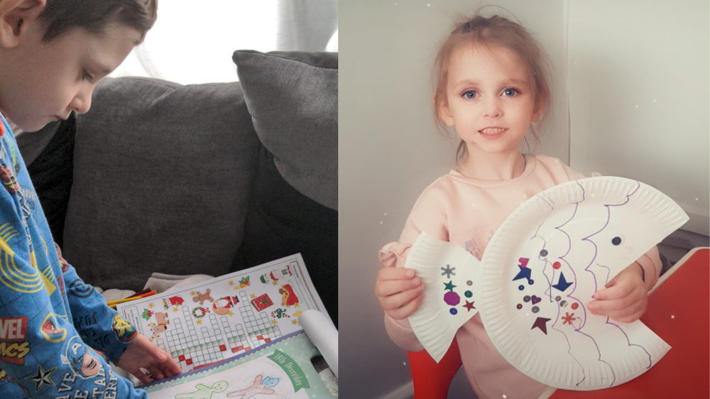 boy holding a colouring book and girl holding a paper fish.png