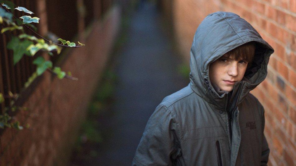 boy in alley looking worried