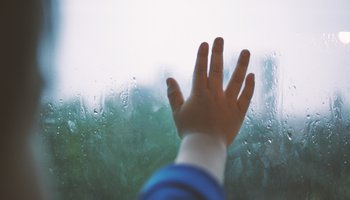 child's hand on rainy window