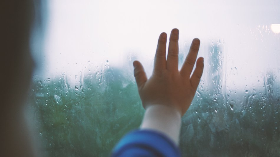 child's hand on rainy window