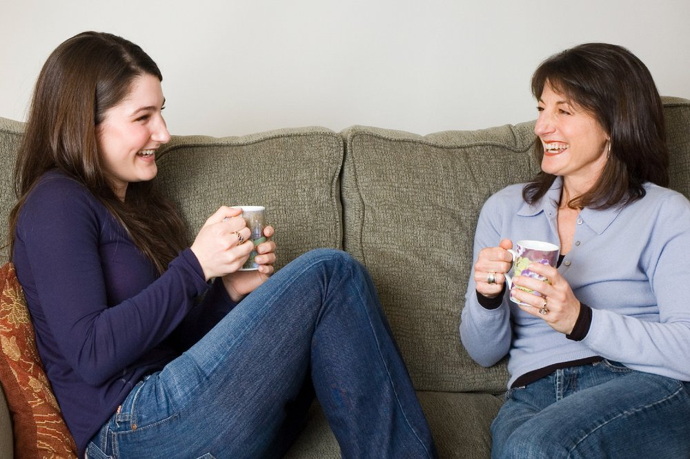 Mother and teenage daughter sitting on sofa and drinking tea together