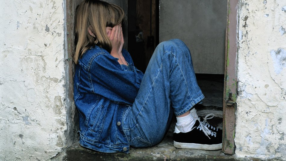 Young girl covering her face in her hands