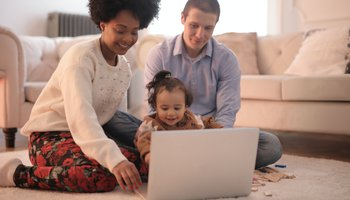 Young couple with baby girl sitting on floor in front of laptop