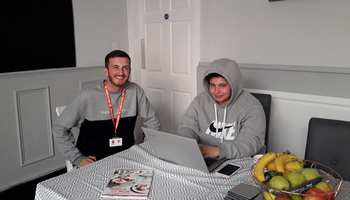 residential service worker and service user sitting at a table.png