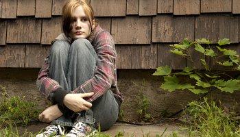Teenage girl outside hands round knees.jpg