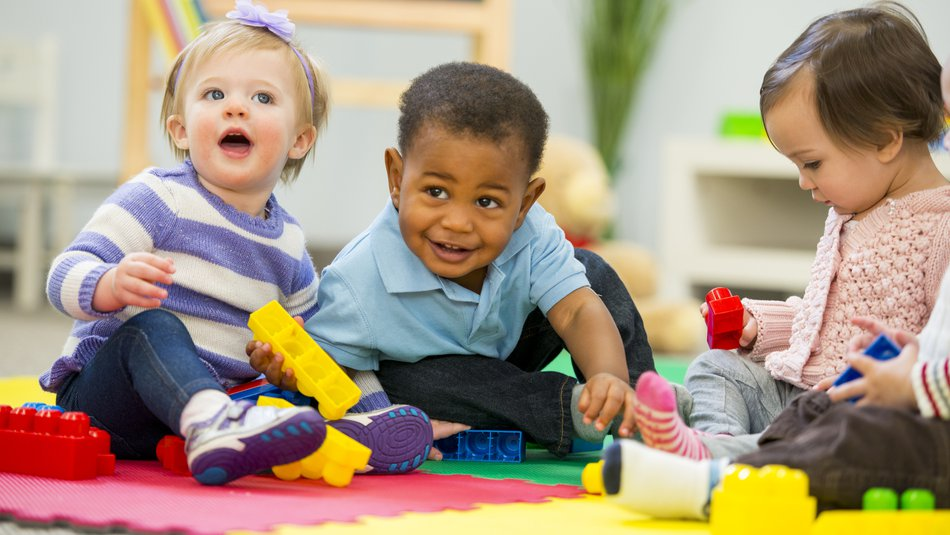 three babies sitting on a colourful mat playing with toy blocks.jpg