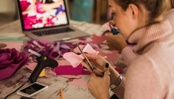 Cutting out flower petals while crafting decorative paper flowers