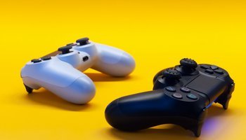 Still photo of video game controllers against bright yellow background