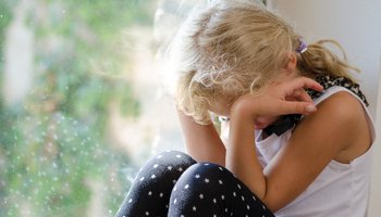 Young  girl sitting by the window and crying