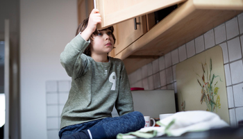 young boy looking in cupboard.png