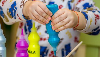 young child squeezing paint bottle.jpg